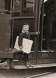 Photo of old-fashioned newsboy, riding a trolley
